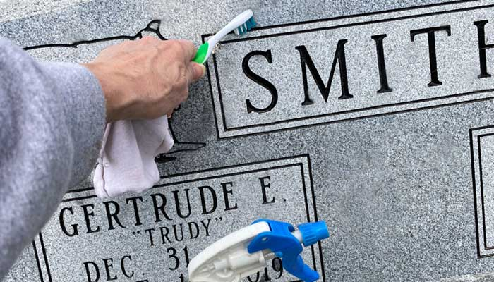 A headstone being cleaned with a toothbrush and mild cleaner.